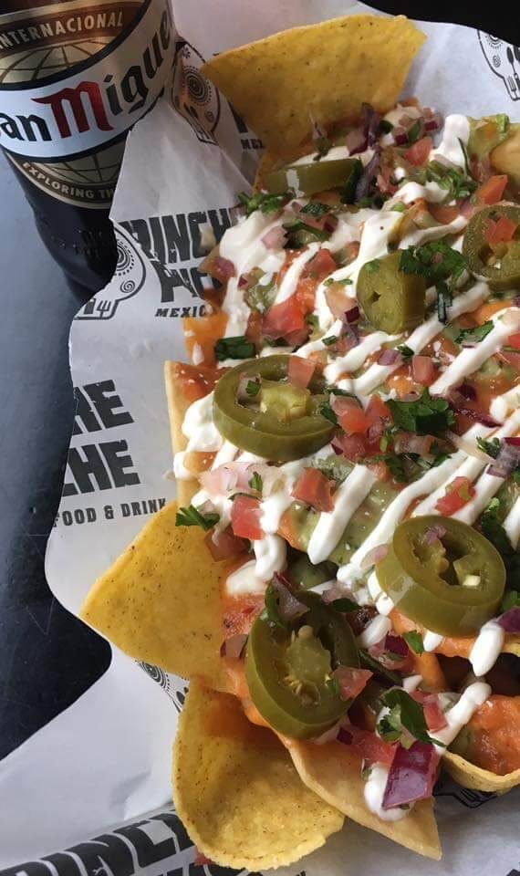 Picture showing nachos made at Pinche Pinche and a bottle of San Miguel